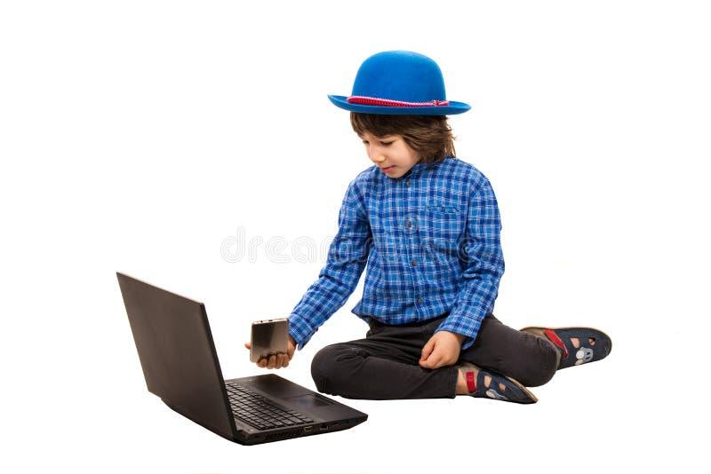 Kleine elegante jongen met laptop en slimme telefoon royalty-vrije stock afbeelding