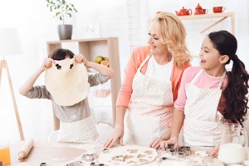 Kleine Enkelkinder täuschen herum in der Küche mit ihrer Großmutter lizenzfreie stockbilder