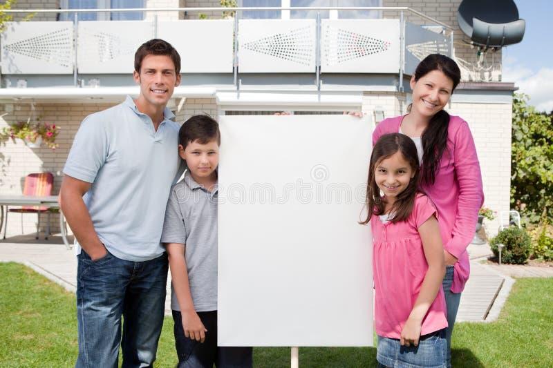 Kleine familie die zich buiten met een leeg teken bevindt royalty-vrije stock afbeeldingen