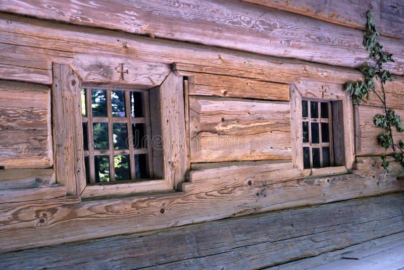 Kleine Fenster in der Wand eines alten Holzhauses lizenzfreies stockfoto