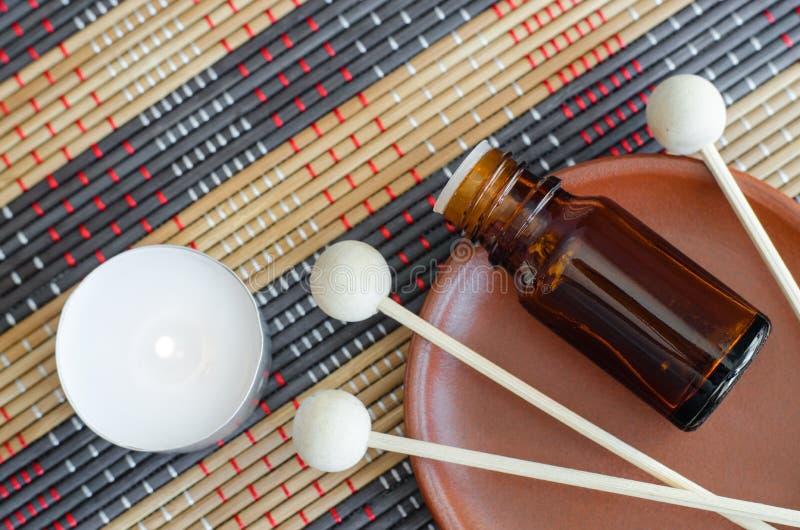 Kleine Flasche mit ätherischem Öl, hölzernen Diffusorschilfen und brennender Kerze auf der Bambusschnurmatte lizenzfreie stockfotografie
