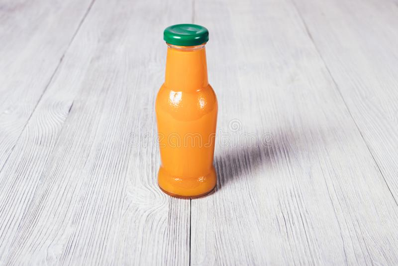 Kleine Flasche Orangensaftstände auf weißem Holztisch stockfoto
