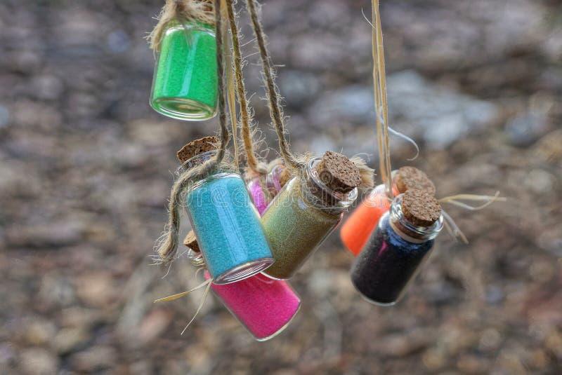 Kleine Flaschen mit farbigem Sandfall auf Schnur stockfotos