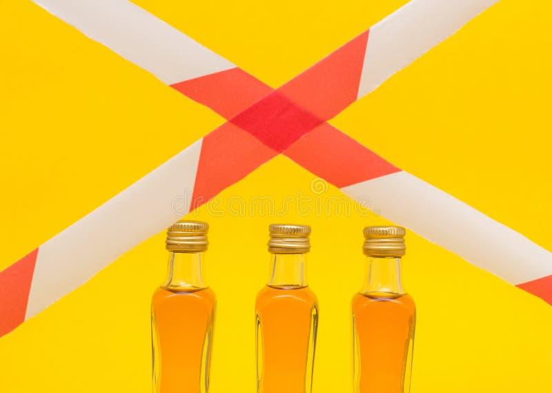 Kleine flessen alcohol op een geel concept als achtergrond en bureaucratische formaliteiten sanctie, dag van gematigdheid, een ve stock foto's