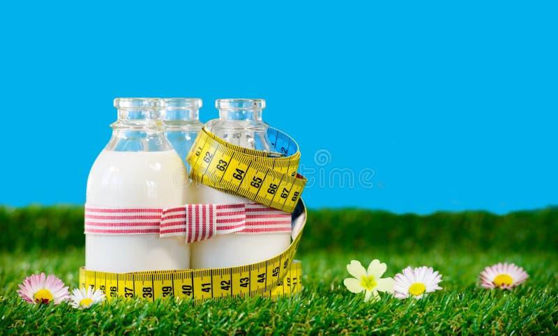 kleine flessen melk met een meetlint royalty-vrije stock foto