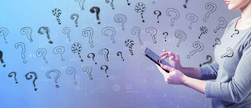 Kleine Fragezeichen mit der Frau, die eine Tablette verwendet lizenzfreie stockfotografie