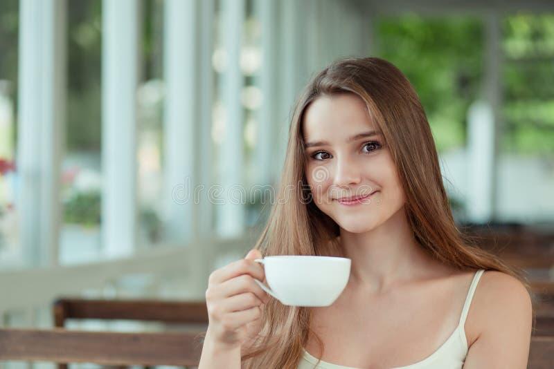 Kleine Frau, die auf der Balkonterrasse eines schicken Cafés sitzt stockbilder