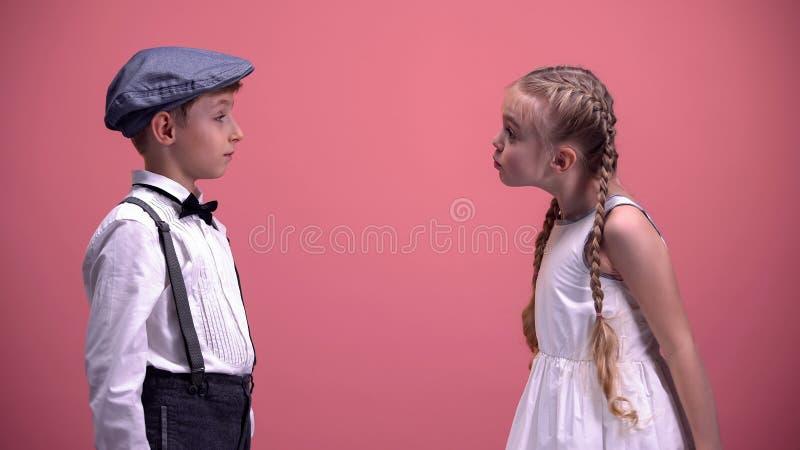 Kleine Freundin, die leidenschaftlich mit dem Jungen, Kinderpaar in der Liebe streiten argumentiert stockbild