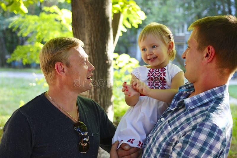 Kleine frohe Tochter mit ihrem Vati und Onkel stockfotos