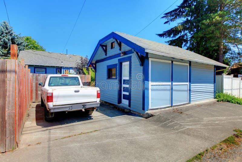 Kleine garage met vrachtwagen en omheining stock afbeelding