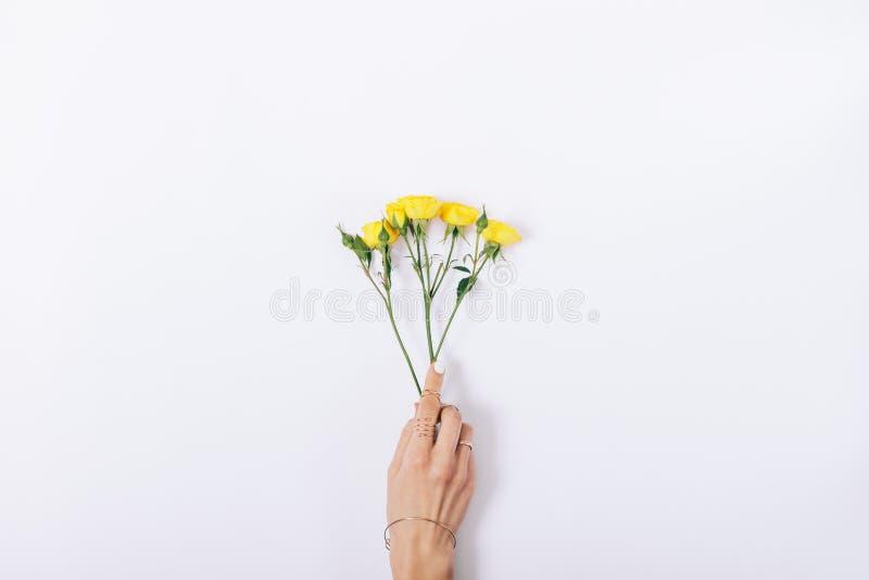 Kleine gelbe Rosen in einer weiblichen Hand lizenzfreies stockbild