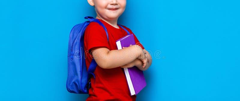 Kleine gelukkige glimlachende jongen met glazen op zijn hoofd, boek in handen, schooltas op zijn schouders Terug naar School Klaa stock fotografie