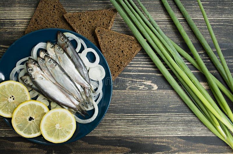 Kleine gesalzene Fische von baltischen Heringen, Sprotten auf einem Holztisch Beschneidungspfad eingeschlossen lizenzfreie stockfotos