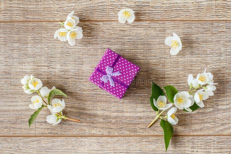 Kleine Geschenkbox eingewickelt mit violettem Band auf Dekor der hölzernen Bretter lizenzfreie stockbilder