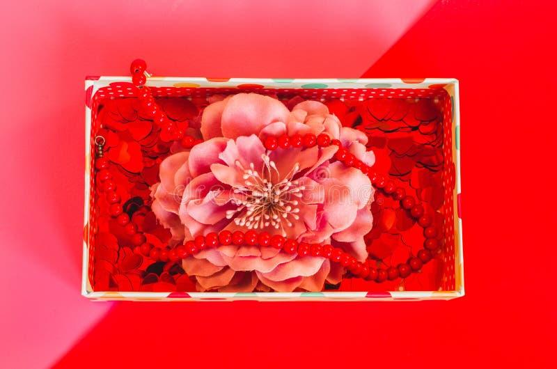 Kleine Geschenkbox mit Blume, wenig Herzen und Perlen auf rosarotem Hintergrund stockfotografie