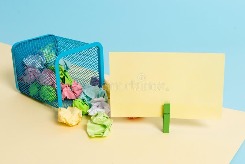 Kleine getipt vuilnisbak vol met gekleurd papier en een clothespin die een kleurrijke papieren noot in een geel en stock fotografie