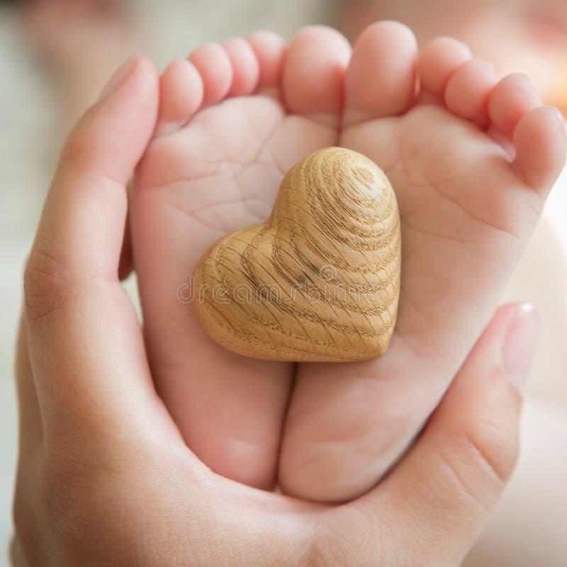 Kleine gevoelige kleine voeten om het houten hart te houden royalty-vrije stock foto's
