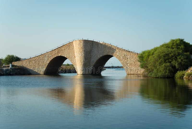 Kleine, gewellte und steile alte Steinbrücke über Mittelmeerküstenwasserweise lizenzfreie stockbilder