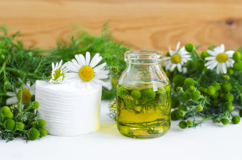 Kleine Glasflasche mit Kosmetik/der Reinigung/heilendes Aromaöl der wilden Kamille und Baumwollauflagen für natürliche Hautpflege lizenzfreie stockfotos