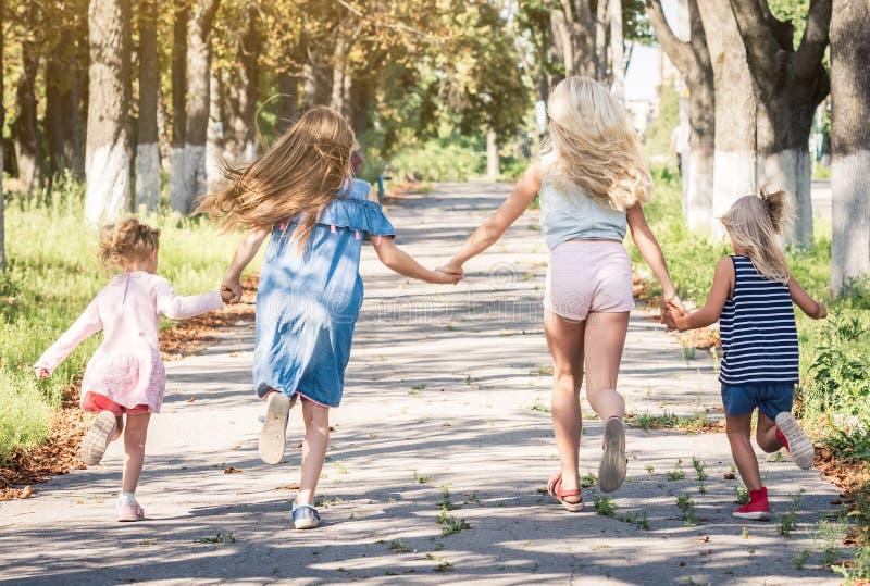 Kleine glimlachende meisjes die op de steeg van de zonneschijnherfst door handen lopen te houden royalty-vrije stock foto's