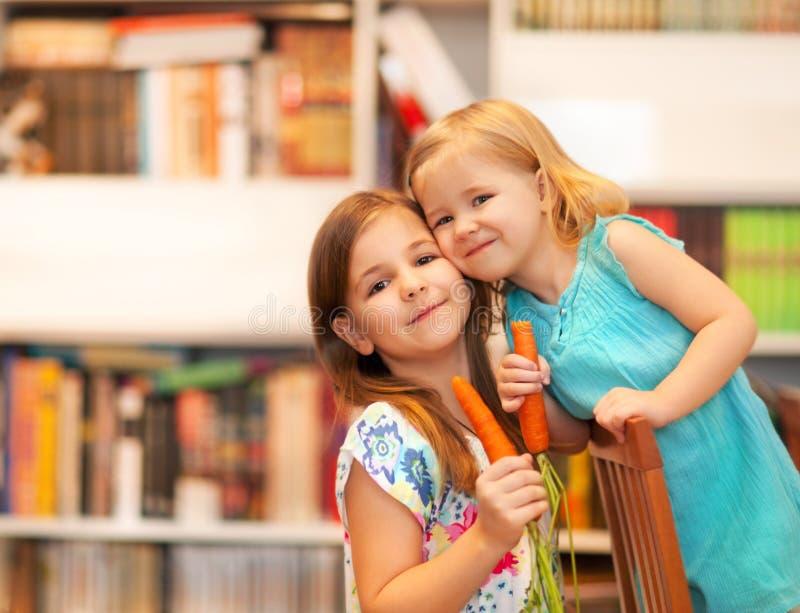 Kleine glimlachende meisjes met wortelen stock foto
