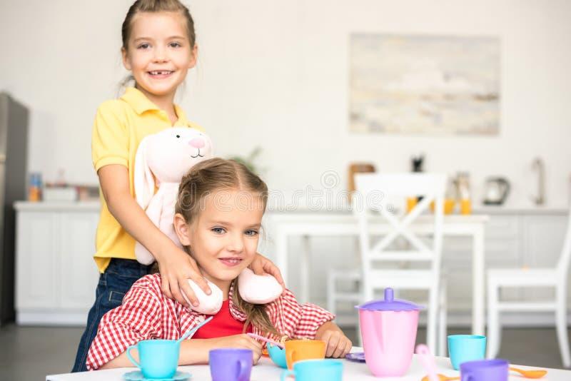 kleine glimlachende zusters die theekransje beweren samen te hebben royalty-vrije stock fotografie