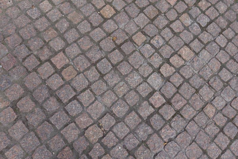 Kleine Granitpflastersteine mit diagonalen Gelenken lizenzfreies stockfoto