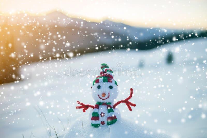 Kleine grappige stuk speelgoed babysneeuwman in gebreide hoed en sjaal in diepe sneeuw openlucht op vaag bergenlandschap en het v royalty-vrije stock afbeelding