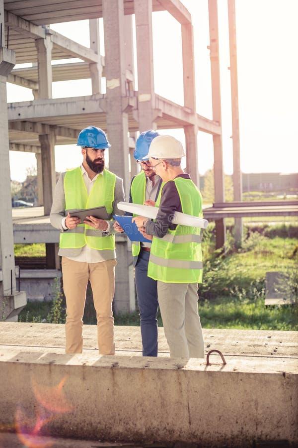 Kleine groep architecten en civiels-ingenieur die op een bouwwerf samenkomen stock afbeeldingen