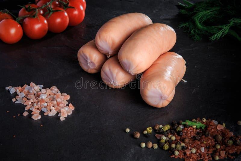 Kleine groep dikke korte worsten met dille en tomaten stock foto's