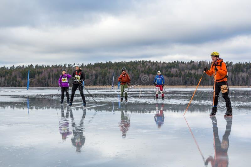 Kleine groep ijsschaatsers op nat en waterig ijs stock foto's