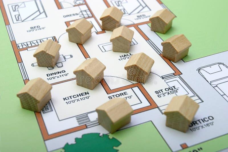 Kleine hölzerne Häuser auf einem Plan lizenzfreies stockbild