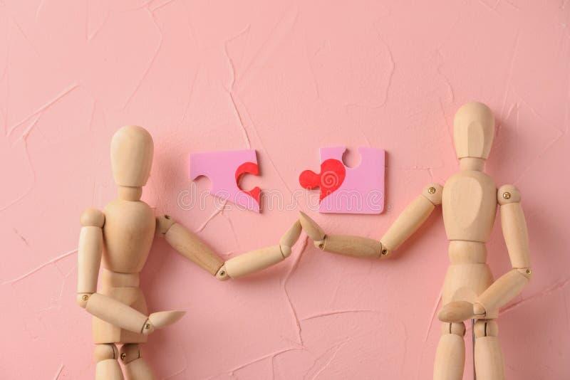 Kleine hölzerne Mannequins mit rosa Puzzlespielen auf Farbhintergrund lizenzfreie stockbilder