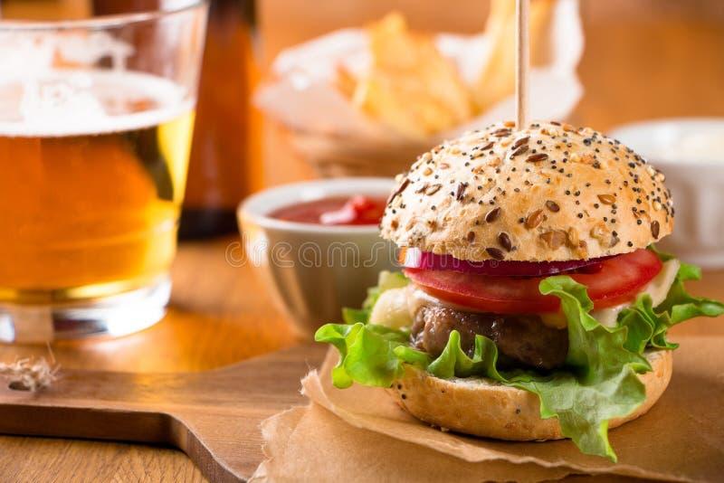 Kleine hamburgersnack met gebraden gerechten en bier stock fotografie