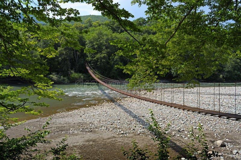Kleine hangbrug door rivier stock afbeeldingen