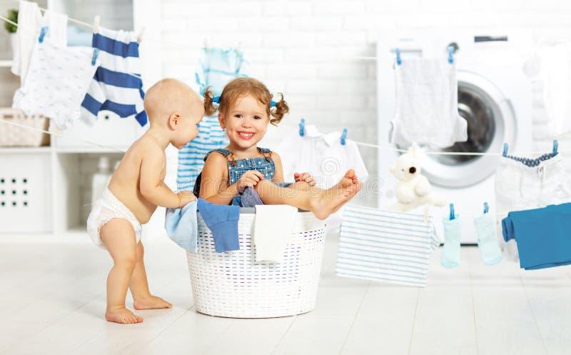 Kleine helpers grappige jonge geitjes gelukkig in wasserij om kleren, pla te wassen royalty-vrije stock afbeeldingen