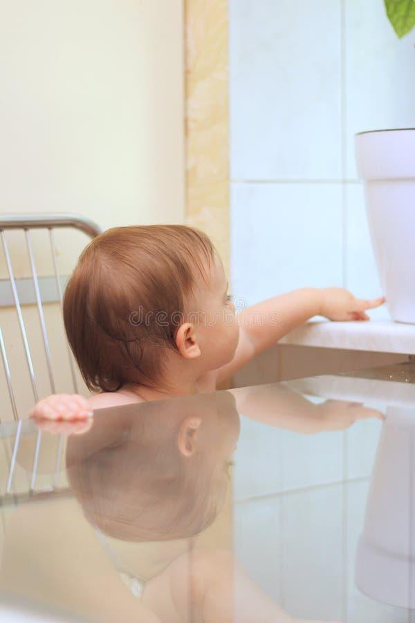 Kleine het glimlachen witte kindzitting op een stoel bij de glaslijst in de keuken dichtbij het venster Het beeld wordt weerspieg stock afbeelding