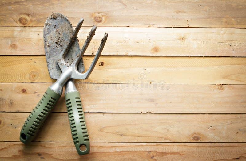 Kleine het tuinieren schop en vork op houten achtergrond stock afbeeldingen