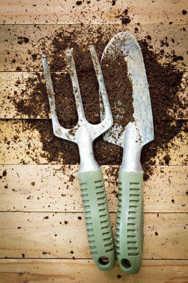 Kleine het tuinieren schop en vork op houten achtergrond royalty-vrije stock fotografie