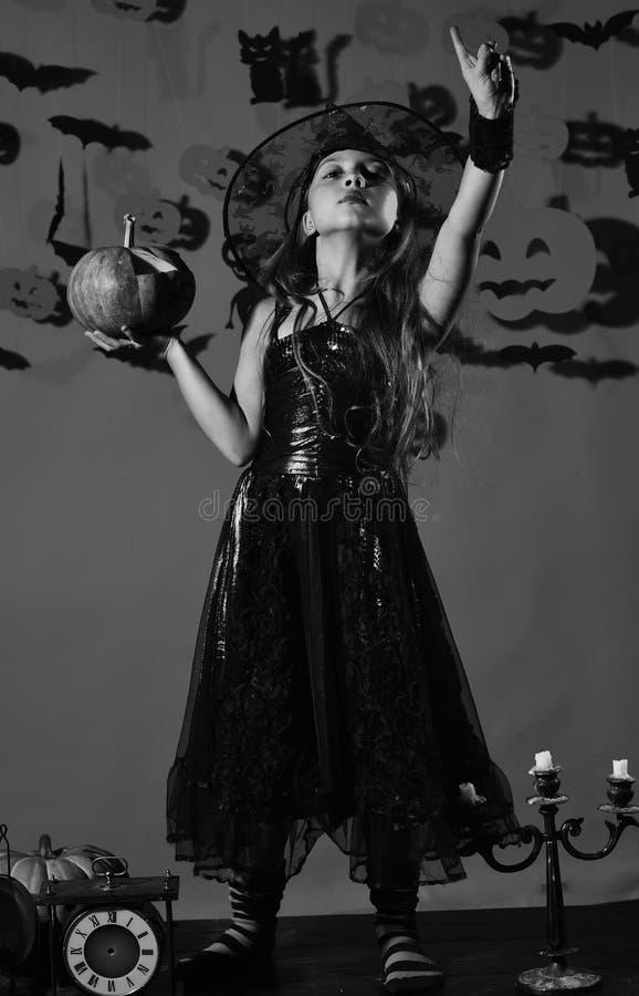 Kleine Hexe, die schwarzen Hut trägt Kind im gespenstischen Hexenkostüm lizenzfreies stockbild