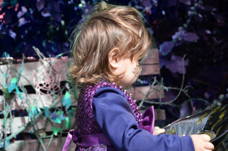Kleine Hexe, ein Mädchen in einem Hexenkostüm, Mädchen gekleidet als Hexe im Wald mit Hut, Halloween lizenzfreies stockbild