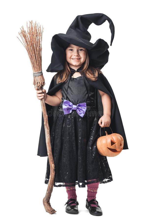 Kleine Hexe mit einem Besen und einem Kürbis stockfotos