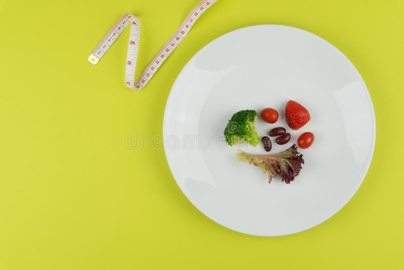 Kleine hoeveelheid voedsel op witte plaat en een metende band royalty-vrije stock foto