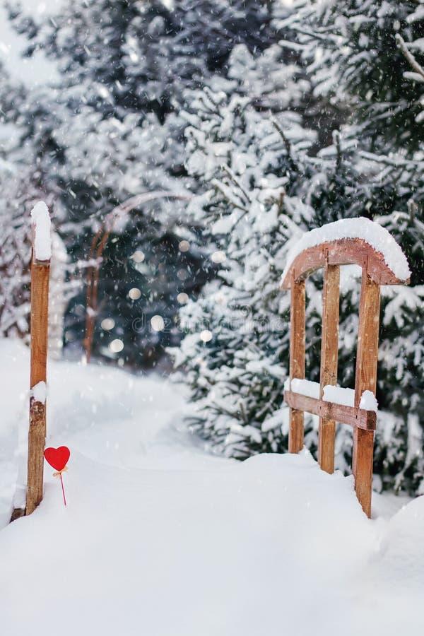 Kleine Holzbrücke unter dem Schnee verziert mit gelesenem Herzen in der unscharfen Winterkiefergasse mit fallendem Schnee stockfotos