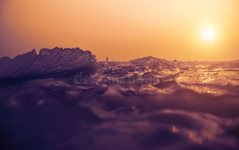 Kleine ijskristallen op bevroren overzees bij zonsondergang stock foto