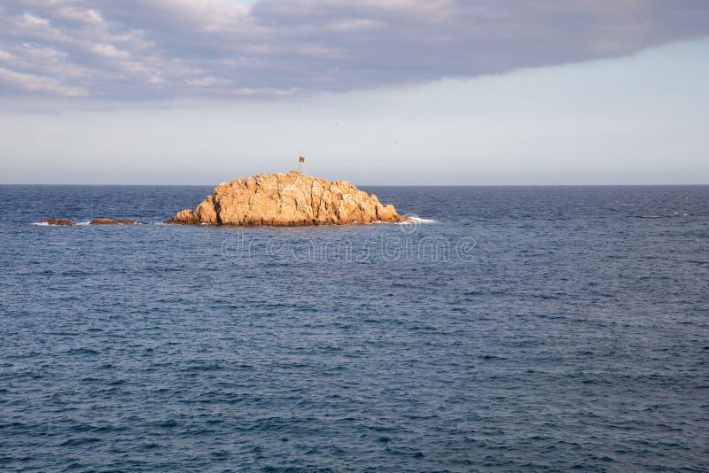 Kleine Insel mit der independentist katalanischflagge lizenzfreies stockbild