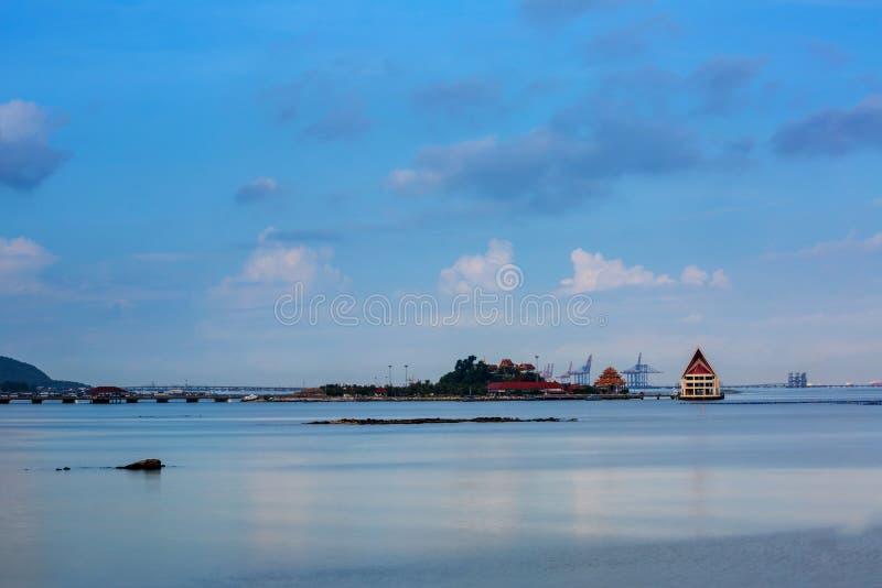 Kleine Insel und Gebäude mit glattem blauem Meer und Reflexion des Himmels mögen Spiegel, Küstenlinie von Sriracha Thailand stockfotos