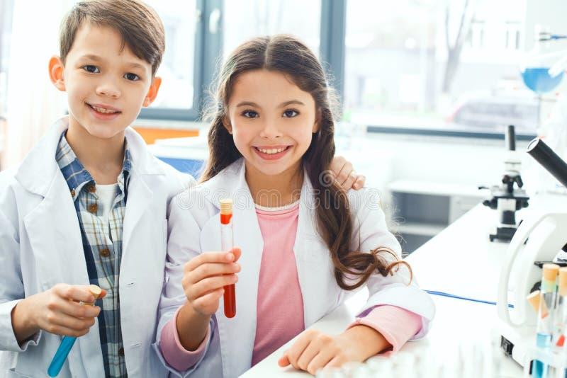 Kleine jonge geitjes die chemie in schoollaboratorium leren die de flesjes van de cameraholding kijken royalty-vrije stock fotografie