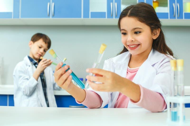 Kleine jonge geitjes die chemie in schoollaboratorium leren die vloeistoffen vergelijken royalty-vrije stock foto
