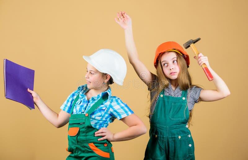Kleine jonge geitjes in helm met tablet en hamer kleine meisjes die samen in workshop herstellen Gelukkige kinderen Toekomstige c stock afbeelding